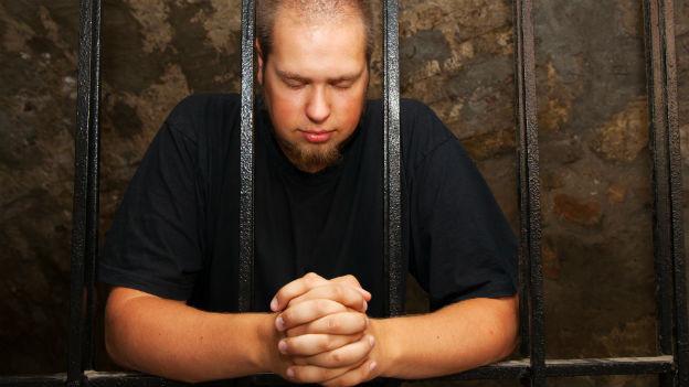 Mann hinter Gefängnisgittern