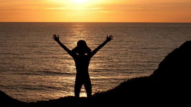 Person am Meer vor Sonnenaufgang