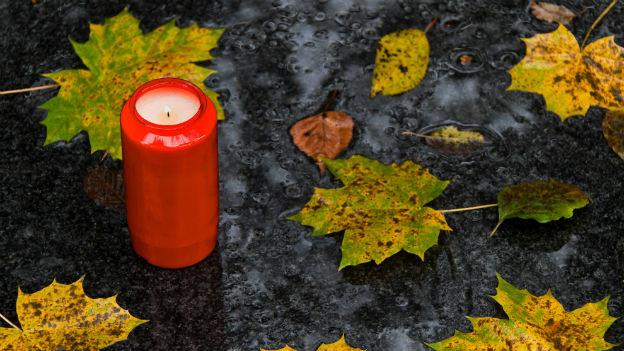 Gedenkkerze auf Laubboden