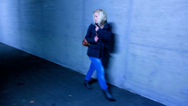 Eine Frau rennt verängstigt durch ein Tunnel