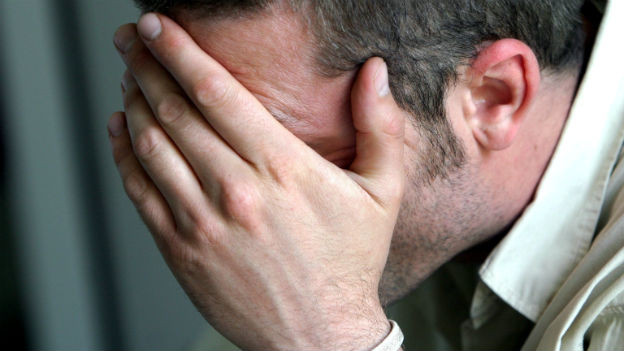 Ein Mann vergräbt sein Gesicht in seinen Händen
