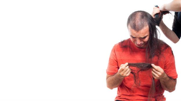 Einem Mann werden die langen Haare abrasiert