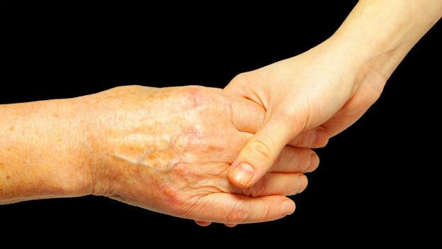 Eine alte Hand greift nach einer jungen.