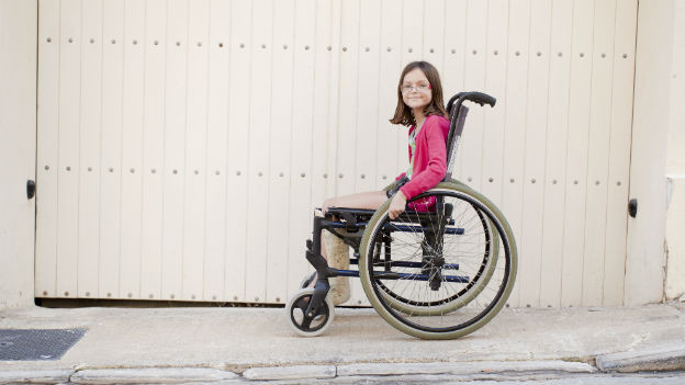 Ein Kind sitzt im Rollstuhl