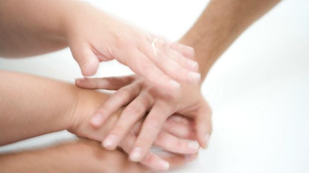 Leute halten Hände übereinander