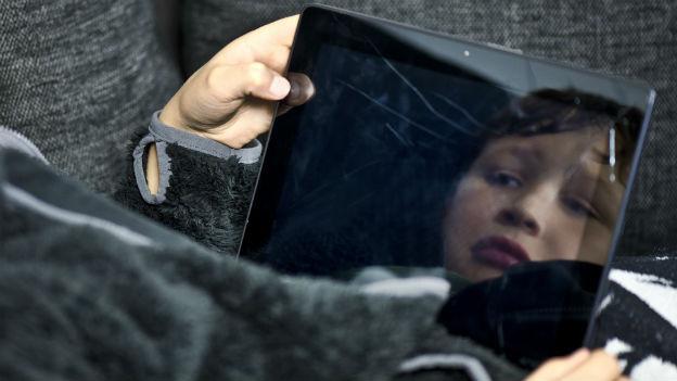 Ein trauriges Kind spiegelt sich im zerbrochenen Tablet