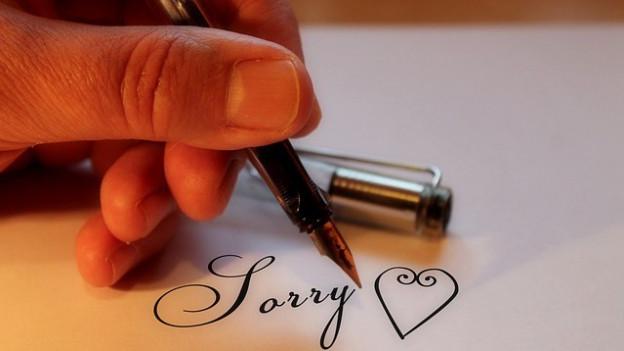 Eine Hand schreibt Sorry auf ein Blatt Papier