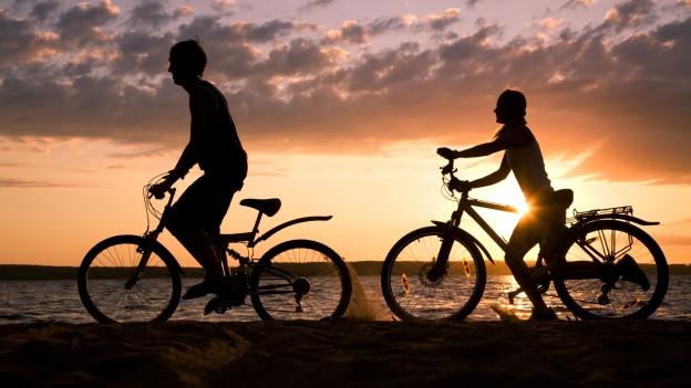 Zwei Radfahrer vor einem Sonnenuntergang