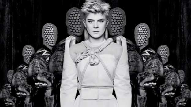 Zu sehen ist eine futuristisch gekleidete Frau in Weiss vor maskenhaften Wesen. Es handelt sich um eine Szene aus einem Musikvideo.