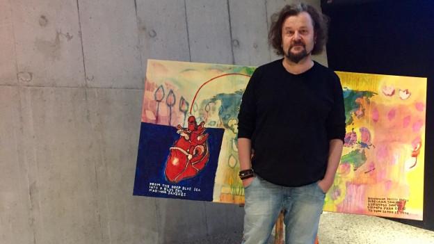 Büne Huber von Patent Ochsner posiert vor seinem Bild, das zum 2018 erscheinenden Album gehören wird