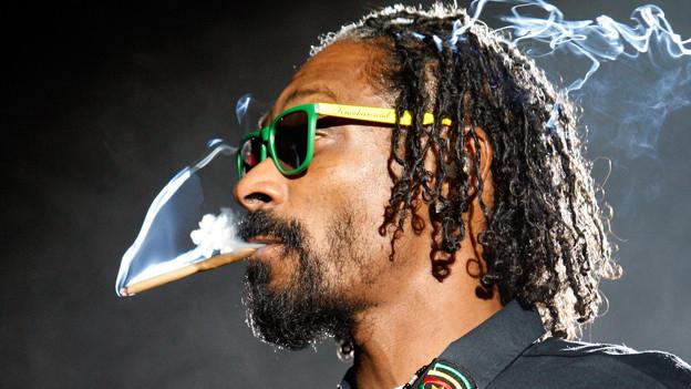 Snoop Dogg rauchend auf der Bühne.