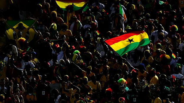 Ghanaische Fussballfans schwenken die Landesflagge.