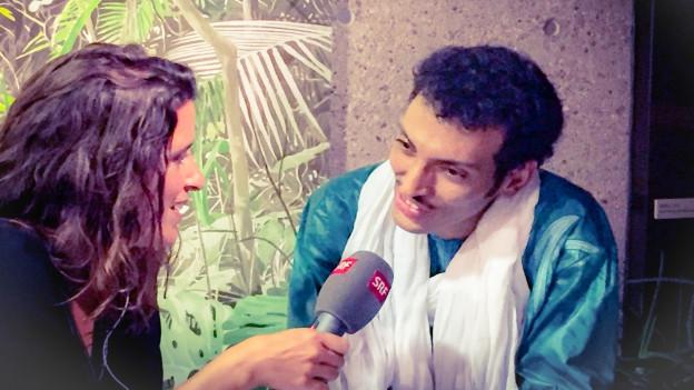 Ein etwas scheu aber charmant wirkender Bombino bittet Rahel Giger im Interview, nach einem gelungen Konzert im Tropenhaus Wolhusen, man möge sein Volk, die Tuareg, nicht vergessen.