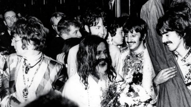 Die Beatles empfangen hier am 26. August 1967 ihren Guru Maharishi Mahesh Yogi am Bahnhof in Bangor, Wales zum Meditationswochenende.