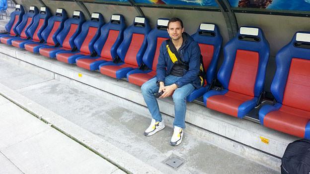 Dort wo sonst die Spieler sitzen: SRF 3 Reporter Manuel Rothmund auf der Bank des FC Basel.