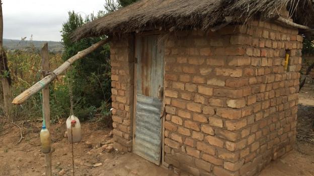 Eine neu gebaute Latrine in Tansania, davor eine einfache Einrichtung, um die Hände waschen zu können.