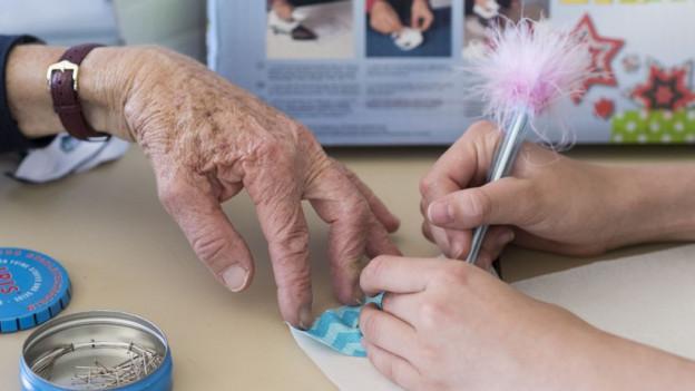 Ein alte und eine junge Hand im Bild.