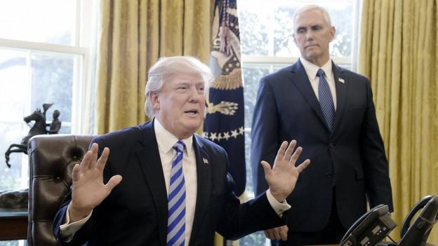 Präsident Trump sitzt am Schreibtisch im Oval Office und hebt die Hände, neben ihm steht sein Vize Mike Pence.