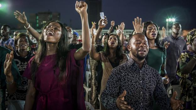 Inbrünstig singende Gläubige im Grossgottesdienst der Pfingstkirche «salvation ministries» in Nigeria.