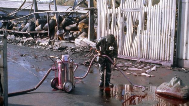 Ein Seuchenspezialist bei der Arbeit nach dem Brand in Schweizerhalle, er spritzt, geschützt mit einer Maske, den Boden ab, hinter ihm Fässer und Trümmer (1. November 1986).