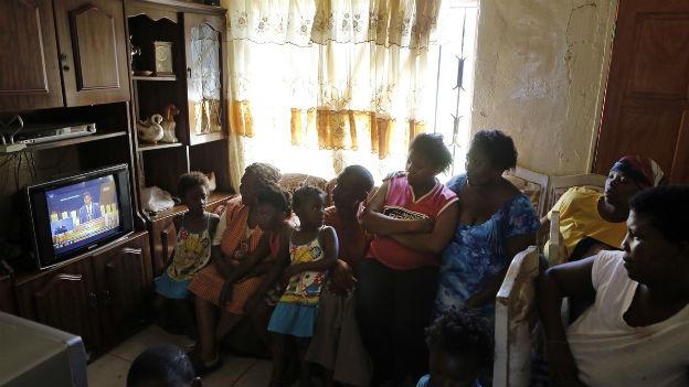 Bewohner des Slums in Soweto verfolgen die Mandela-Trauerfeier