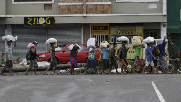 Opfer des Taifuns in Tacloban schleppen Säcke mit Hilfsgütern.
