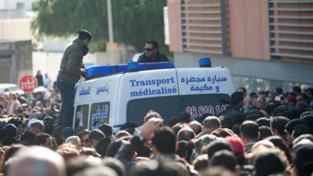Der Leichnam von Belaïd wird in der Menge abtransportiert.