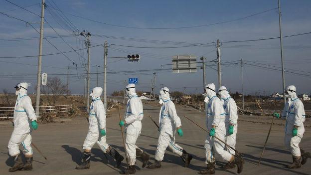 Japanische Polizisten in Schutzanzügen am 7. April 2011 suchen nach Opfern der Nuklear-Katastrophe von Fukushima