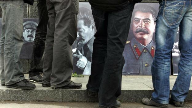 Passanten in Russland betrachten Bilder von Josef Stalin.