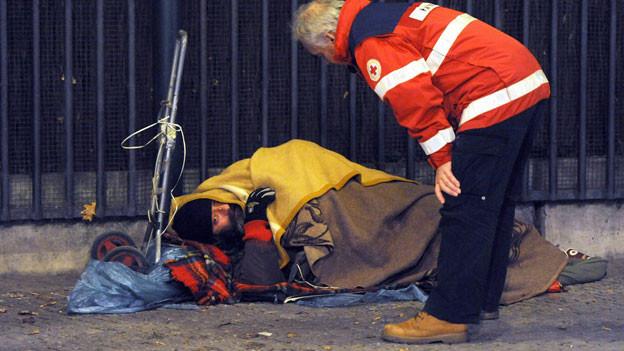 In Deutschland hat nicht jeder ein Dach über dem Kopf. Ein Rotkreuz-Mitarbeiter spricht mit einem Obdachlosen in Berlin.