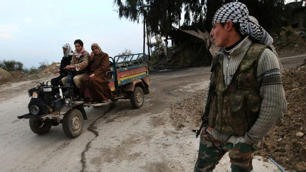 Ein Anti-Assad-Kämpfer beobachtet Dorfbewohner an einem Checkpoint bei Yacobiyeh in der syrischen Provinz Idlib im Nordwesten des Landes