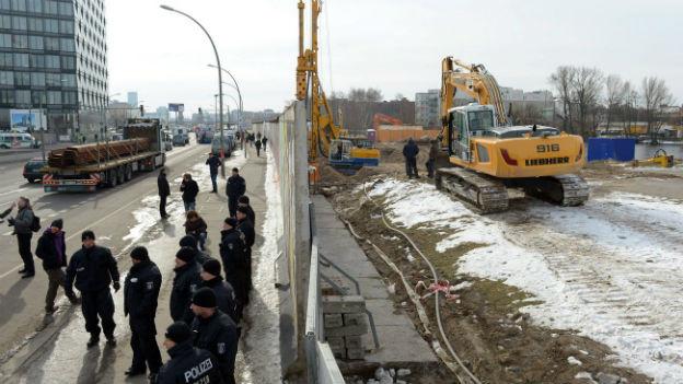 Polizisten schützen die Baustelle.