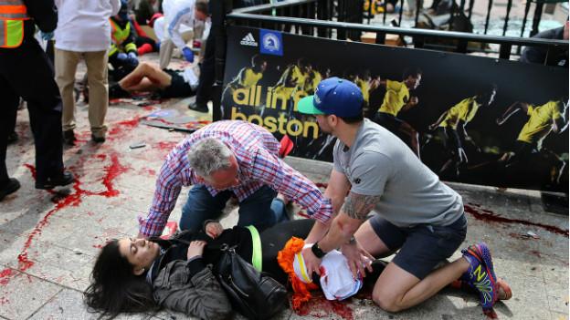 Anschlag in Boston: Helfer kümmern sich am Marathon um eine verletzte Frau.