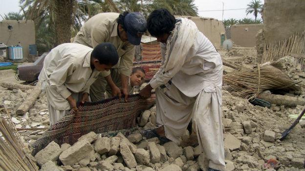 Überlebende versuchen,  einen Teppich aus den Trümmern zu ziehen.
