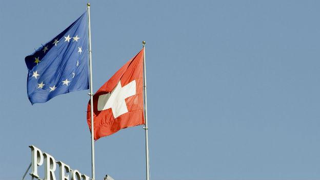 Die Schweizerfahne und die Fahne der EU auf dem Dach des Hotels Wilson in Genf