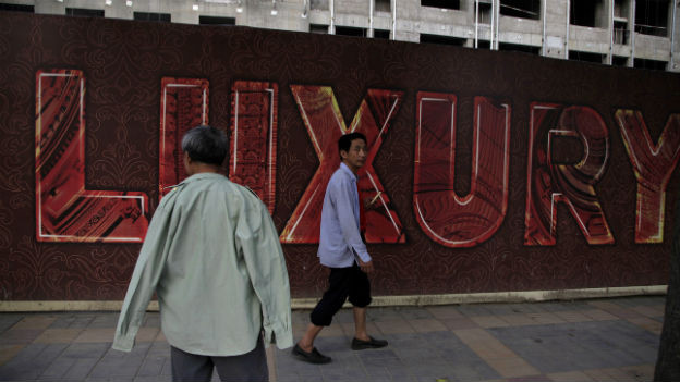 Ein chinesischer Wanderarbeiter vor einem Luxus-Zentrum in Peking