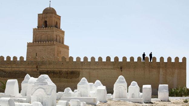 Tunesische Polizisten wachen auf der Oqba ibn Nafa Moschee in der Stadt Kairouan, am 19. Mai 2013. Unterstützer der islamistischen Hardliner-Gruppe Ansar al-Scharia kämpften mit der tunesischen Polizei, nachdem die Regierung eine jährliche Kundgebung verboten hatte.