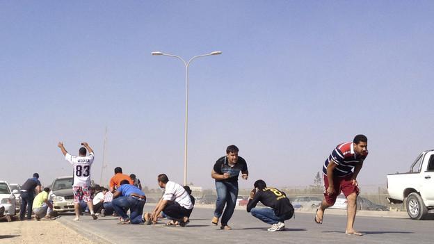 Demonstranten vor der Kaserne einer Miliz gerieten ins Kreuzfeuer und suchten Deckung hinter Fahrzeugen.