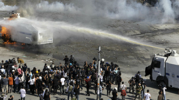 Die Polizei löscht einen in Brand gesteckten Wasserwerfer auf dem Taksim-Platz in Istanbul.