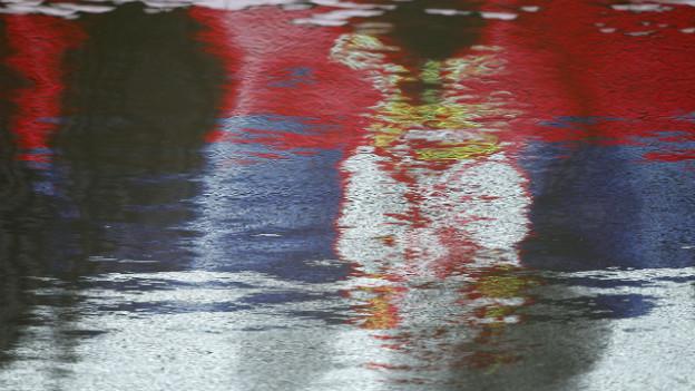 Die serbische Flagge spiegelt sich im Wasser eines Sees: Serbien macht heute einen grossen Schritt in Richtung EU.