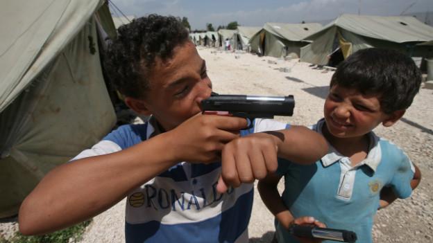 Syrische Kinder spielen in einem Flüchtlingslager in Libanon mit Spielzeugpistolen.
