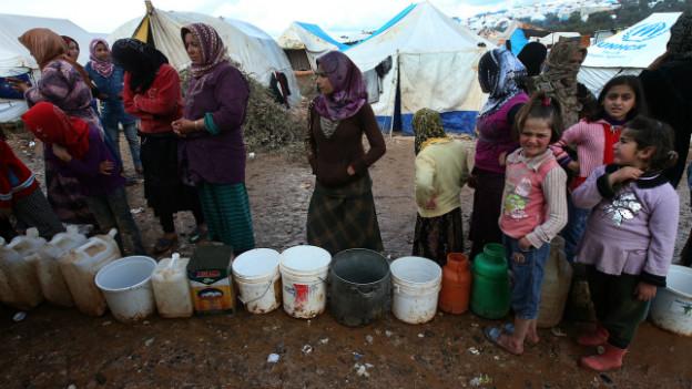 Syrische Flüchtlinge warten in einem Flüchtlingscamp darauf, ihre Eimer mit Wasser zu füllen.