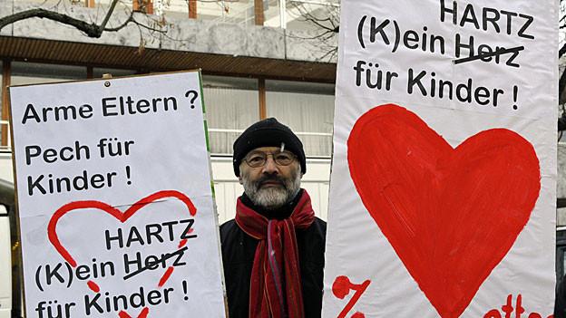 Ein Mann protestiert am 9. Februar 2010 vor dem Bundesverfassungsgericht in Karlsruhe - vor der Urteilsverkündung zu den Hartz IV-Regelsätzen für Kinder.