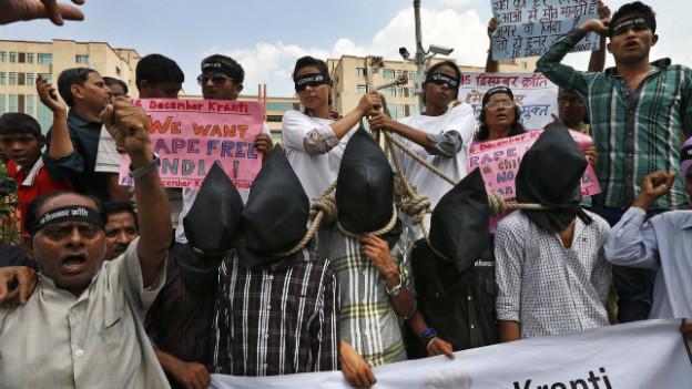 Demonstranten fordern mit einer Hinrichtungsszene die Todesstrafe für die Vergewaltiger.