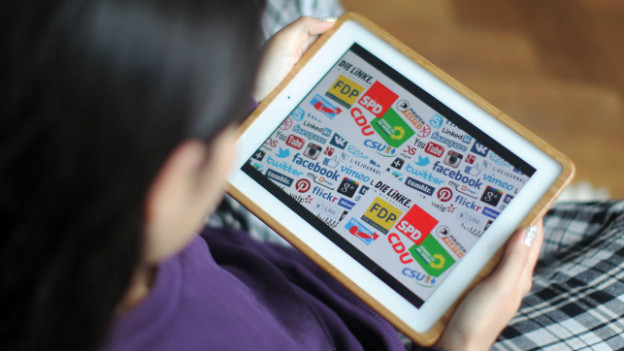 Wahlkampf in Deutschland: Parteilogos auf einem Tablet-Computer.