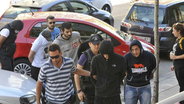 Tatverdächtige werden nach dem Mord an einem Rapper in Griechenland abgeführt.