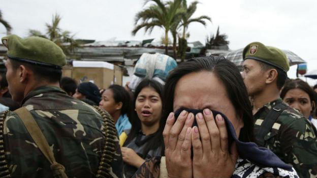 Eine Überlebende vor einem Transportflugzeug in Tecloban.