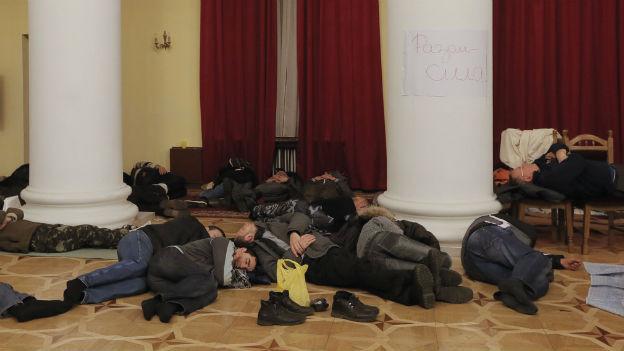 Ukrainische Demonstranten ruhen sich in einem besetzten Gebäude in Kiew aus.