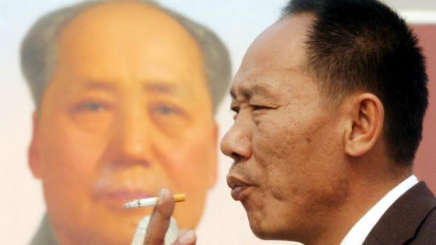 Ein Chinese raucht - im Hintergrund das Protrait von Mao.