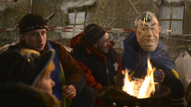 Wenigstens die Gummimaske mit dem Konterfei von Janukowitsch sorgt für Heiterkeit bei den Demonstranten.